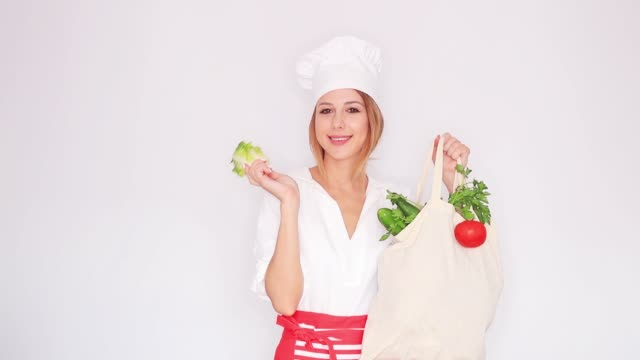 woman in cook uniform holding with different vegetables video