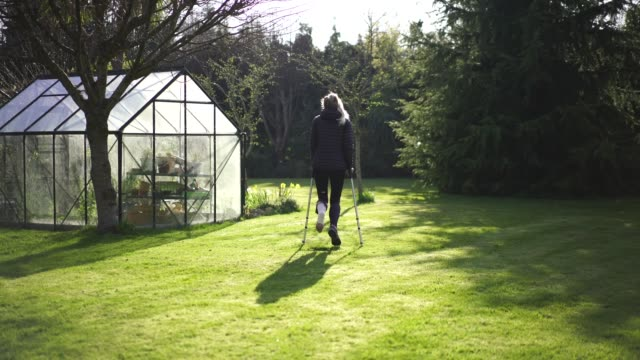 Woman in crutches with cast walks through garden Recovering from injury crutch stock videos & royalty-free footage