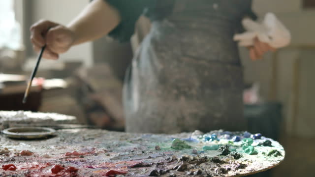 woman in dirty apron takes oil paint drawing in art studio - imperfection stock videos & royalty-free footage