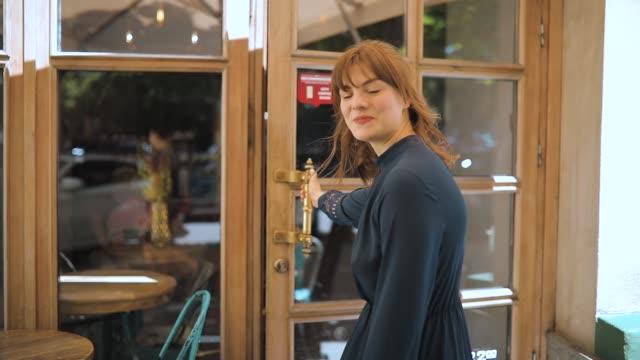 Woman in dress like doorman open the door and invite in cafe video