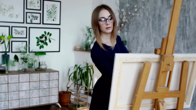 Woman in dress painting in a studio video