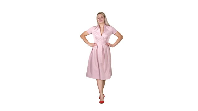 Woman in dress with hands on hips walking while looking at camera on white background
