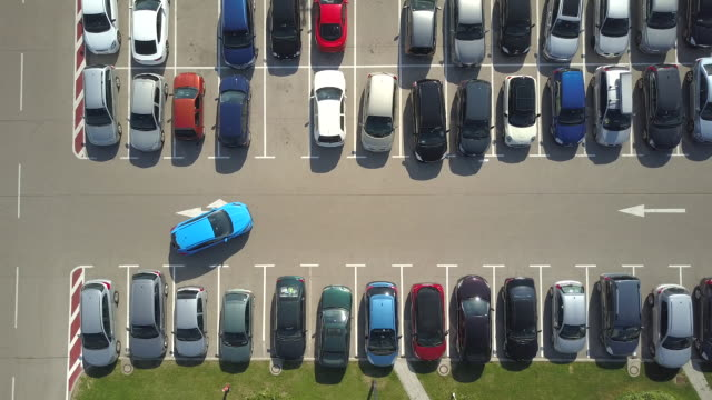 AERIAL: Woman in driving-school learning how to park a car in parking lot space video