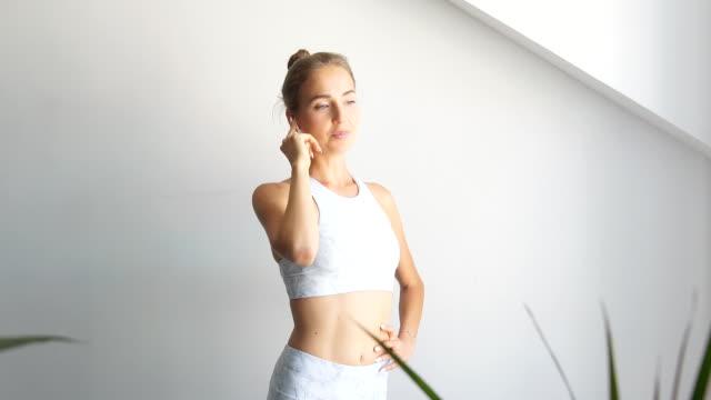 donna in auricolari che guarda la macchina fotografica e sorride sopra il muro bianco - auricolari wireless video stock e b–roll
