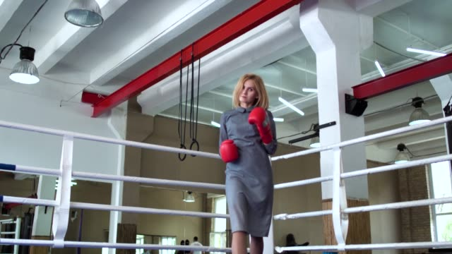 Woman in elegant dress and boxing gloves show professional hits at camera video