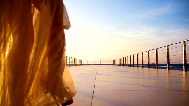 woman in evening dress leaves on a terrace on the background of the sea woman in evening dress leaves on a terrace on the background of the sea human joint stock videos & royalty-free footage