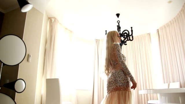 woman in evening dress standing in oval living room video