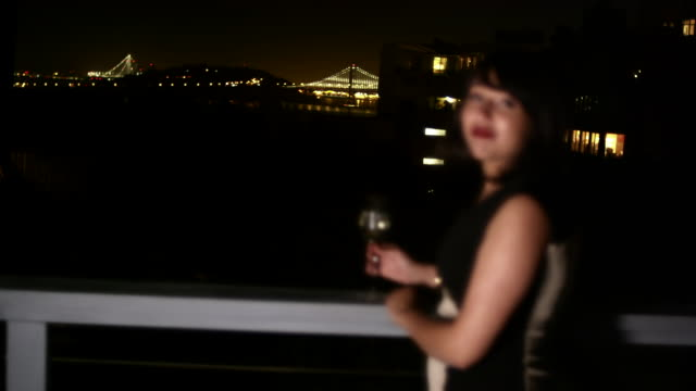 A woman in evening wear stands on a roof and smiles at the camera with a glass in her hand at night video