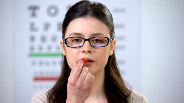 Woman in eyeglasses applying lip balm and smiling to camera, confident lady Woman in eyeglasses applying lip balm and smiling to camera, confident lady eye chart stock videos & royalty-free footage