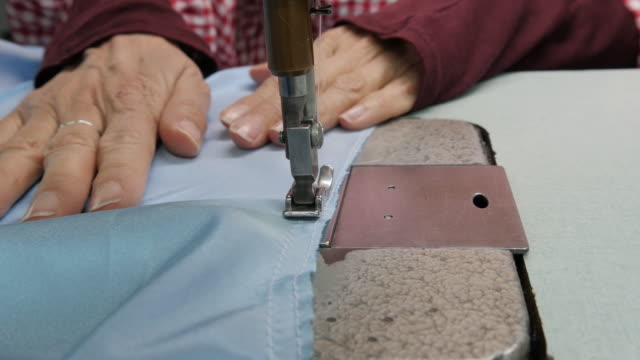 CU Woman in factory sewing video