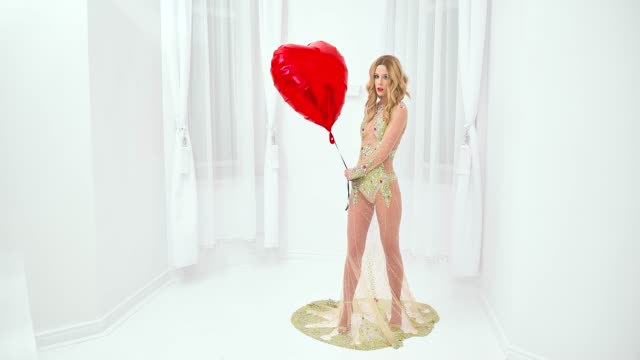 Frau in modischem Kleid hält Herzform Ballon – Video