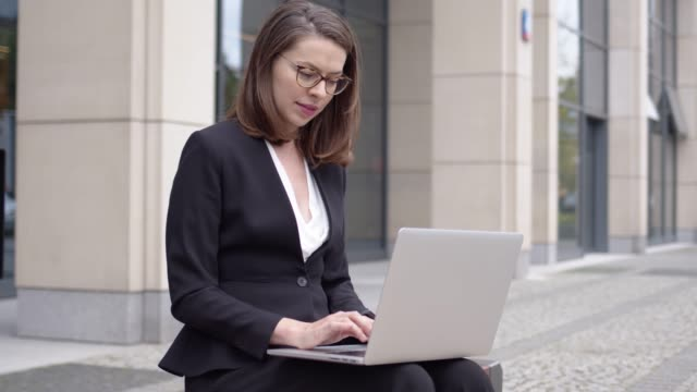 Woman in formal attire using laptop outside office building
