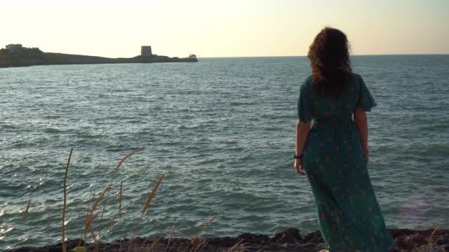 イタリアの夕暮し時のトラブッコを眺めながら海景の前にいる女性 - 漁師 外人点の映像素材/bロール