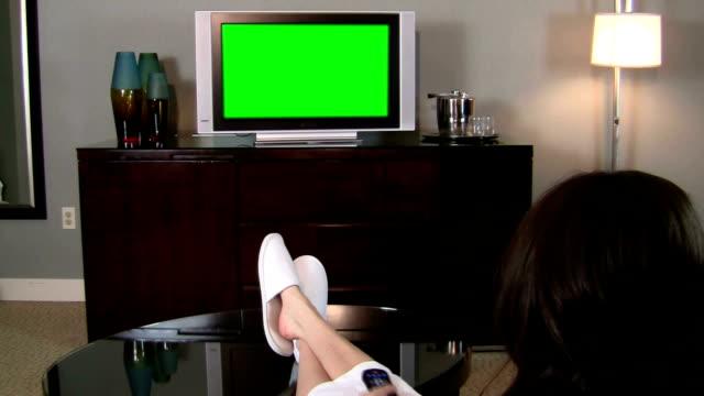 vidéos et rushes de femme en face de la télévision haute définition avec écran vert - peignoir