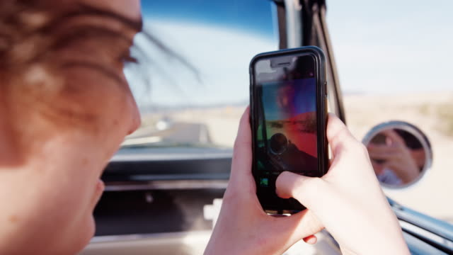 Woman in front passenger seat of open car filming with phone Woman in front passenger seat of open car filming with phone filming stock videos & royalty-free footage