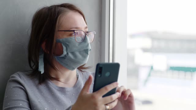 Woman in glasses and mask near the window during quarantine video