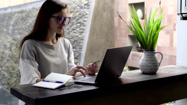 woman in glasses buy on flight on laptop with credit card in beautiful interior. - conto corrente video stock e b–roll
