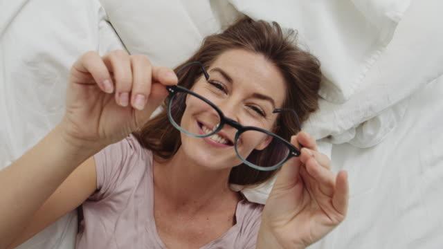 frau in brille im bett liegend - brille stock-videos und b-roll-filmmaterial