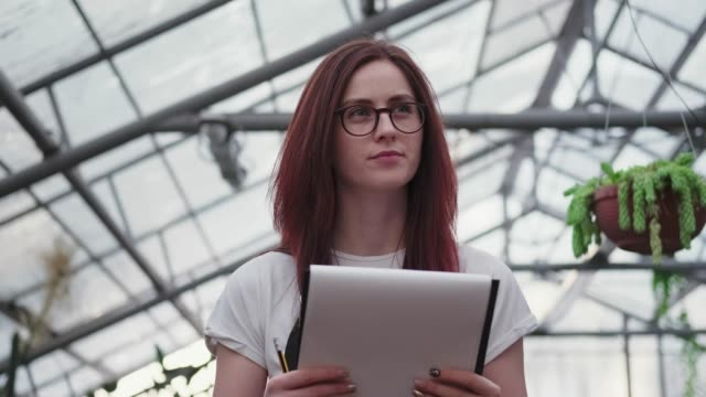 Woman in glasses on the background of the glass roof of the greenhouse