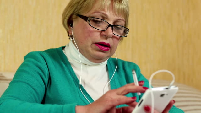 Woman in glasses with white smartphone smoking a cigarette video
