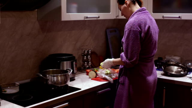 Woman in gloves cleans zucchini in the kitchen video