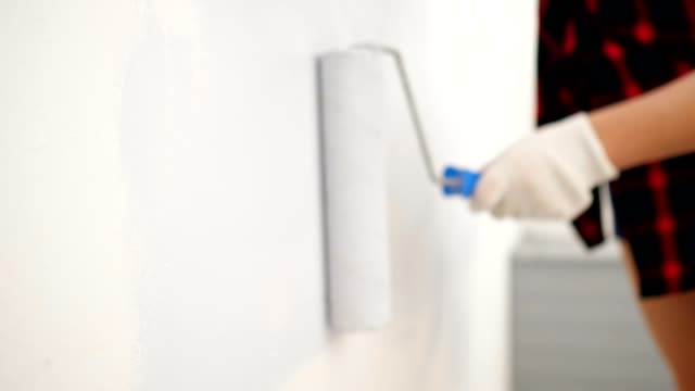 woman in gloves paints wall in light grey color with roller