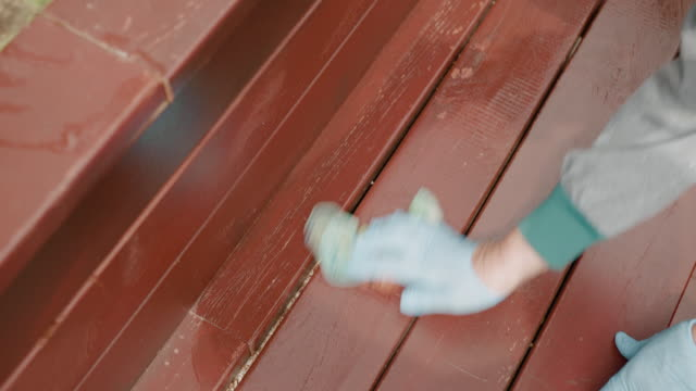Woman in gloves washing wooden surface brown color outdoor. Top view housewife cleaning wooden bench in summer garden.