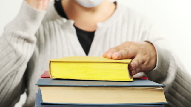 woman in gray clothes and a medical mask sits behind a stack of books and turns the pages, then takes off the mask and puts it on the book