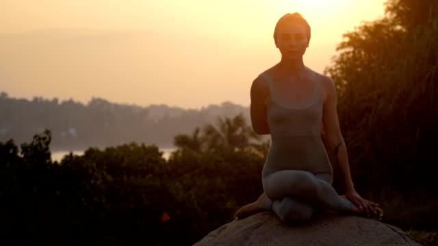 frau in grau steht in gomukhasana auf alten stein zeitlupe - niedrig stock-videos und b-roll-filmmaterial