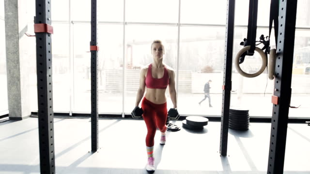 Woman in gym go with dumbbell video