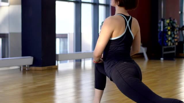 ジムで女性が足を伸ばすために突進の運動 - 女性選手点の映像素材/bロール