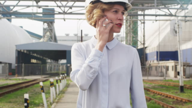 vídeos de stock e filmes b-roll de woman in hard hat walking and talking on phone in industrial environment - plano charriot