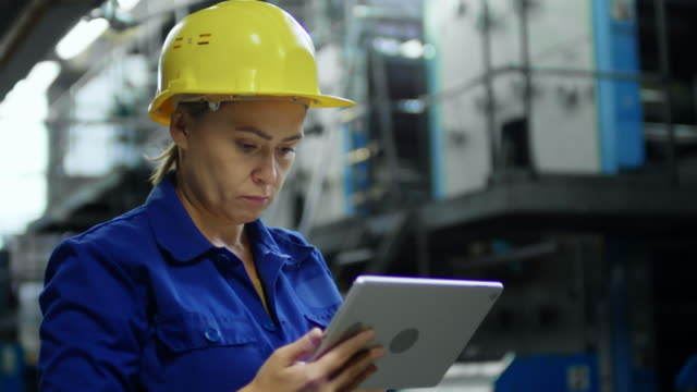 Bидео Woman in Hardhat Working with Tablet Computer