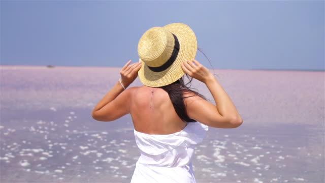 vidéos et rushes de femme dans la promenade de chapeau sur un lac de sel rose sur une journée ensoleillée d'été. - lac salé