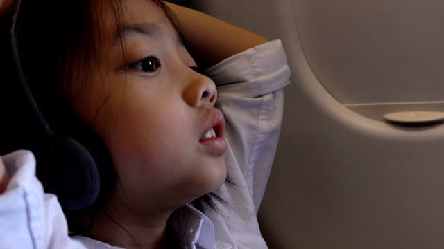 Woman in headphones during fly in airplane video