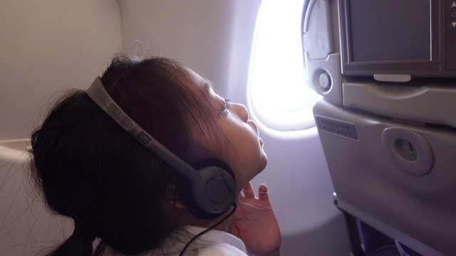 vidéos et rushes de femme dans les écouteurs lors de vol en avion - prise avec un appareil mobile