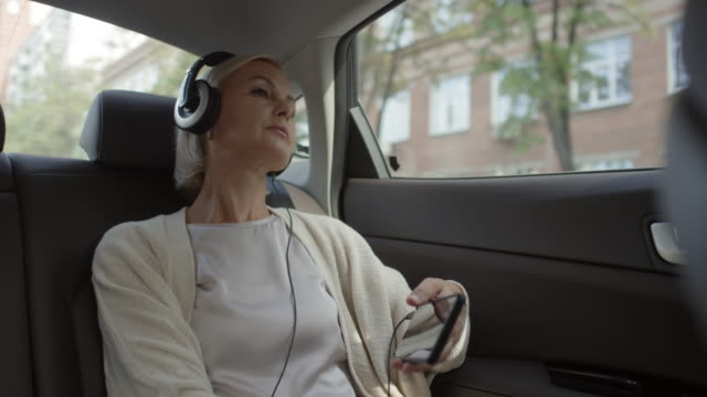 Video Woman in Headphones Looking through Car Window and Listening to Music on Phone