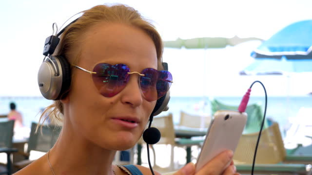 Woman in headset video chatting on mobile Close-up shot of young woman in heart-shaped sunglasses wearing headset and having a video chat on smart phone. Happy girl showing beach to the talker and blowing kiss finishing the chat hands free device stock videos & royalty-free footage