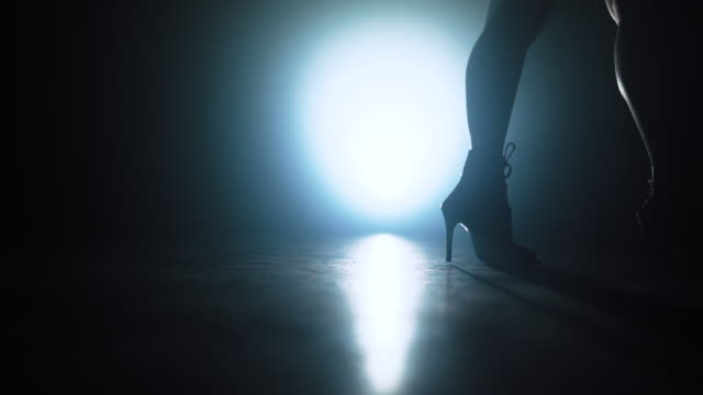 woman in heels walks near camera across spotlight on smoky stage. girl in sexy clothing. nightclub dancer concept. - seduzione video stock e b–roll