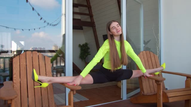 Woman in high heels doing splits between two chairs Lovely flexible young woman in stylsh high heels and leggings practicing side splits between two chairs on terrace in the morning. Graceful fitness female sitting on twine, doing stretching exercises. doing the splits stock videos & royalty-free footage
