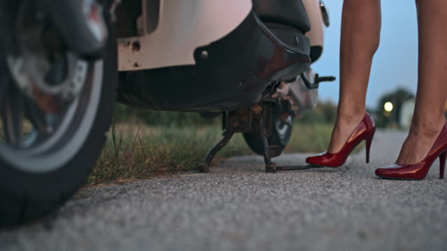 SLO MO Woman in high heels parking a scooter