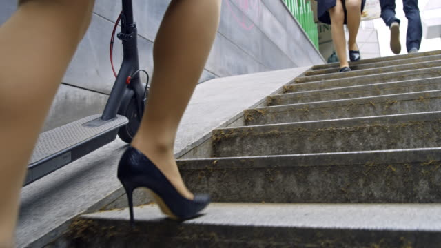 SLO MO Woman in high heels pushing an electric scooter on stairs out of underpass Slow motion shot of an unrecognizable woman in a skirt and high heels pushing an electric scooter on stairs out of the underpass. Shoot in 8K resolution. alternative fuel vehicle videos stock videos & royalty-free footage