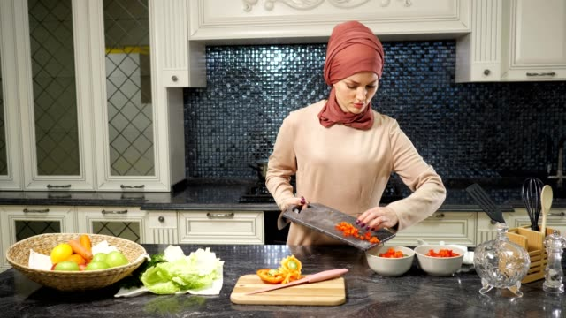 woman in hijab stands at kitchen table cutting vegetable