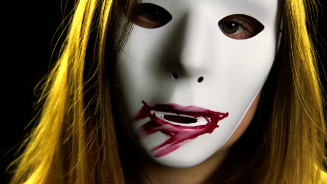 Woman in horror mask painting lips Woman in horror mask painting lips mask disguise stock videos & royalty-free footage