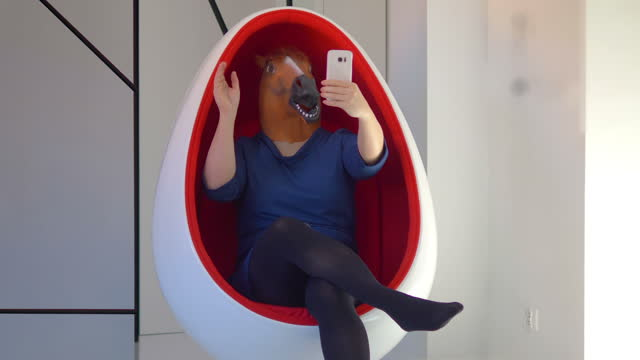 Woman in horse mask taking selfie in 4k slow motion 60fps video