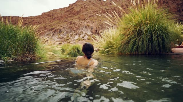 Woman in hot spring in Atacama desert Young Caucasian woman swimming  in hot spring in Atacama desert desert oasis stock videos & royalty-free footage
