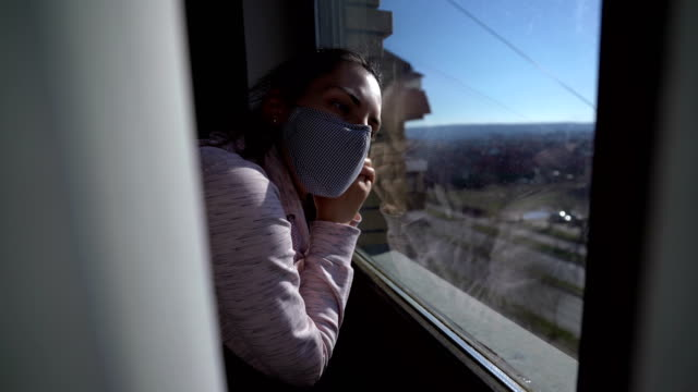 woman in isolation at home - hand on glass covid video stock e b–roll