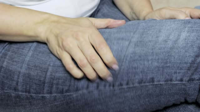 Woman in jeans scratches her leg by hand close up