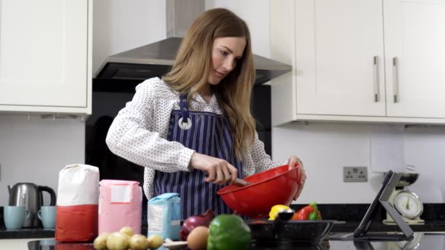 vidéos et rushes de femme dans la cuisine à la maison suivant la recette sur la tablette numérique - recette