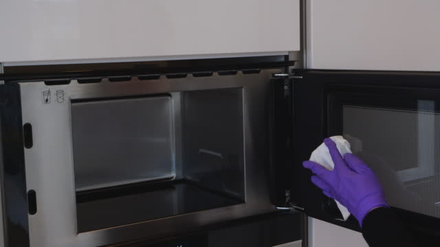 Woman in kitchen cleaning microwave